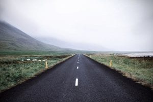 Wide Open Road Surrounded by Green Grass and Mountain