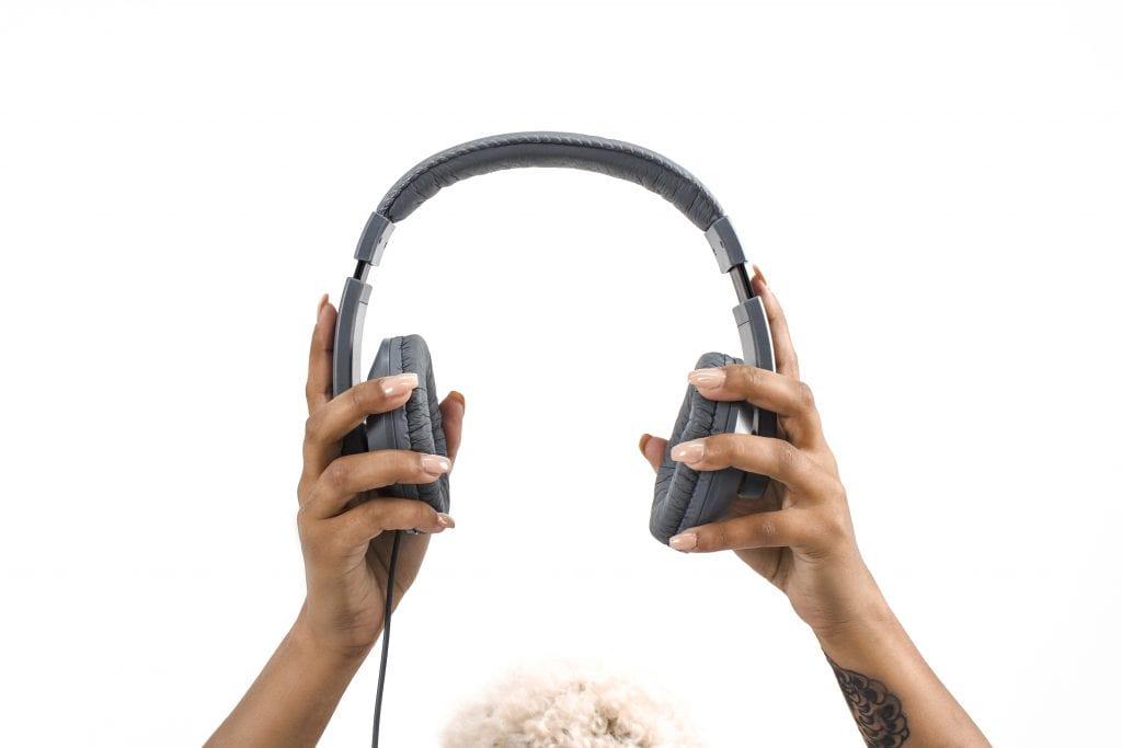 two hands holding headphones