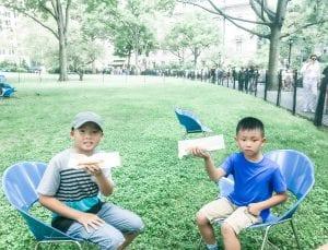 Boys enjoying a NYC hotdog in Battle Park