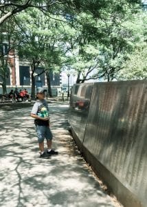 Boy looking at the American Immigrant Wall of Honor