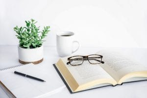 This photo has a book, glasses, coffee cup, notebook and plant on a concrete desk