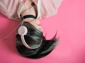 woman listening to music with pink headphones on