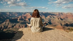 woman meditating overlooking the Grand Canyon