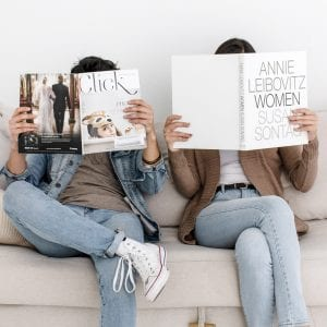 man holding a magazine and woman holding a book on a couch