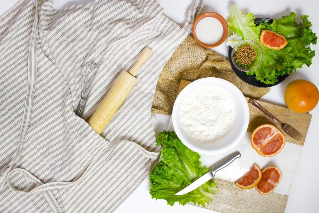 table with apron, lettuce, orange, flour