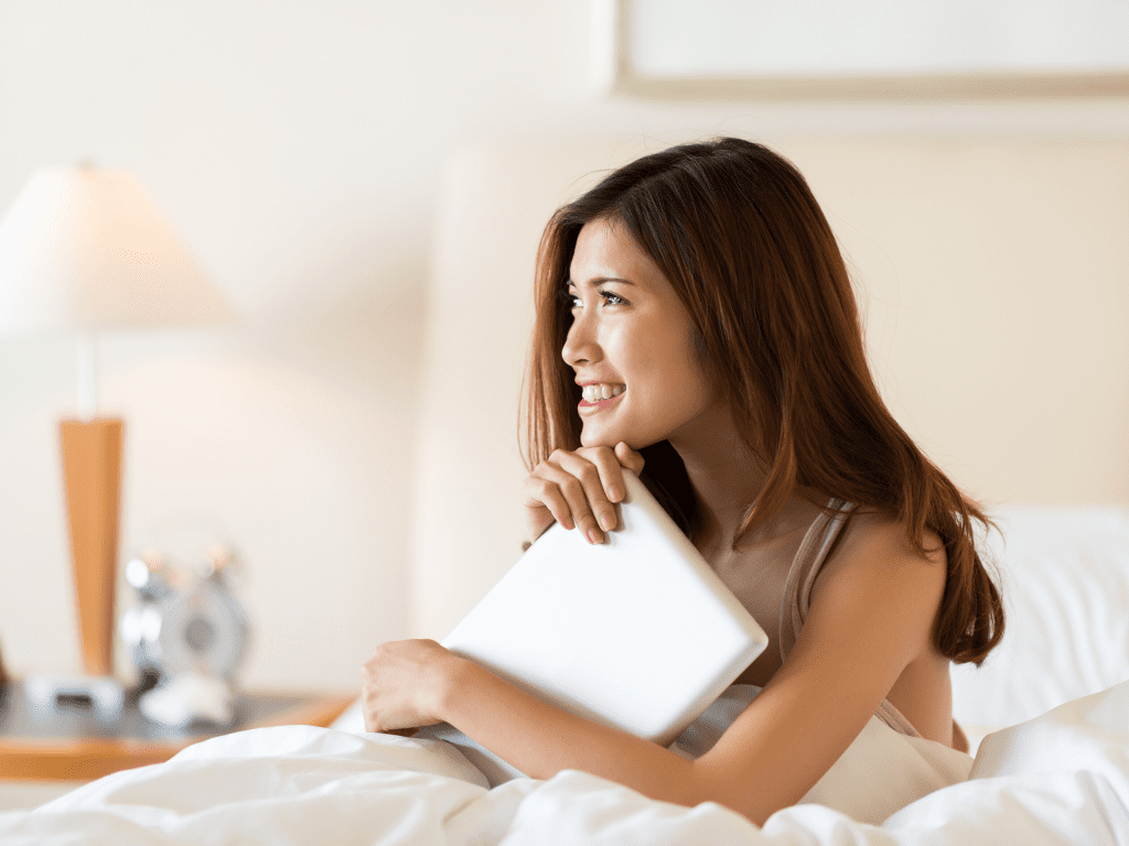 woman sitting in bed thinking positive thoughts