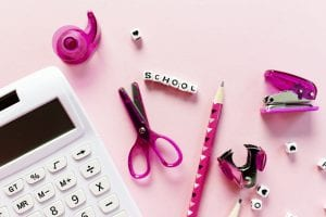 pink table with calculator, scissors, pencils
