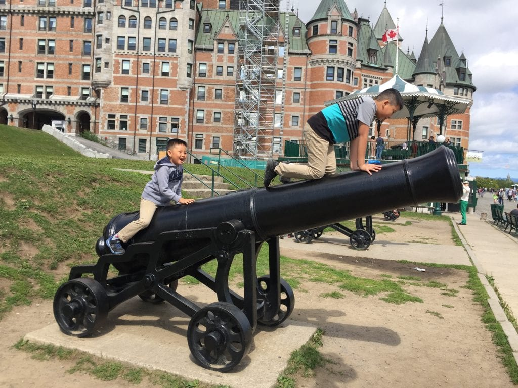 Quebec City with kids - boys climbing on cannons on Dufferin Terrace